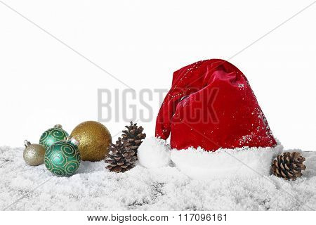 Santa Claus hat with baubles and cones on a snowy table over white background