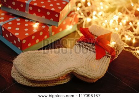 Golden Christmas lights, gift box and warm wool socks on wooden background, close up
