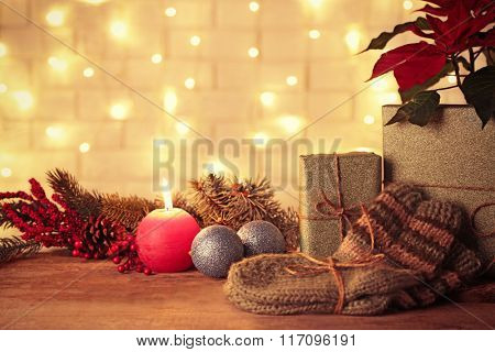 Pair of knitted socks with wrapped gifts for Christmas on brick wall background
