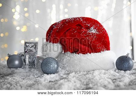Santa Claus hat with baubles and gift boxes on a snowy table over glitter background