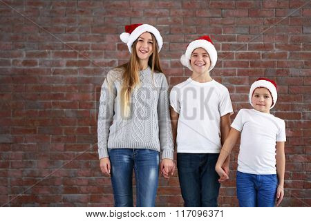 Boys and girl in Santa hats in a row on brick wall background