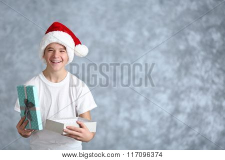 Cute boy with blue gift box on grey background