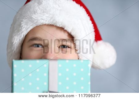 Portrait of cute boy with blue gift box, close up