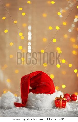Santa Claus red hat with Christmas decorations on the artificial snow against shiny background, close up