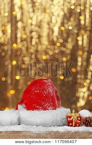Santa Claus red hat with Christmas decorations on shiny background, close up