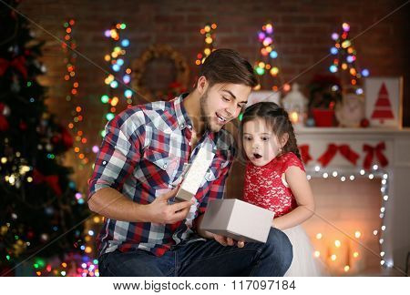 Older brother and little sister opening gift in Christmas living room