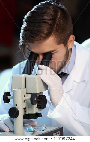 Serious clinician studying chemical element in laboratory