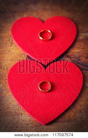 Two red felt hearts and wedding rings on wooden background closeup