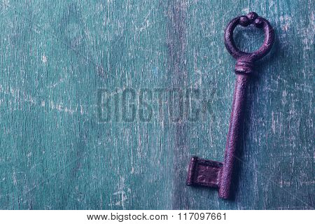 Old keys on green scratched wooden background, copy space