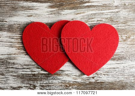 Red felt hearts on grey wooden background