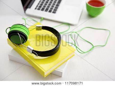 Headphones and laptop on white table, closeup