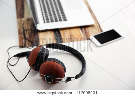 Headphones, phone and laptop on white table, closeup