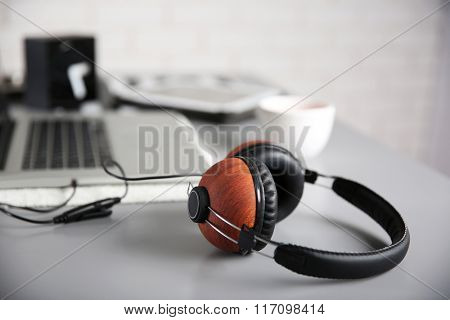 Headphones and laptop on gray table against defocused background