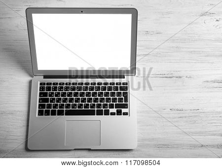 An open silver laptop on white wooden background
