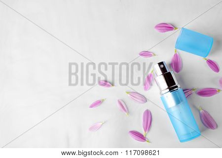 Bottle of perfume and rose petals on fabric background