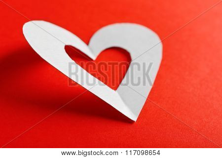 Cut out white paper heart on red background