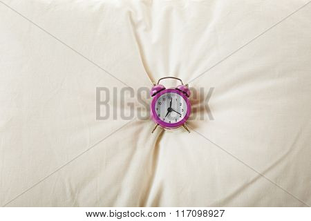 Alarm clock on pillow, close up