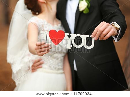 Happy wedding couple holding inscription with heart