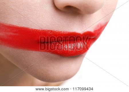 Woman's face with smeared red lipstick isolated on white, close up
