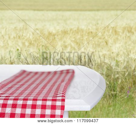 White wooden table with napkin on field background