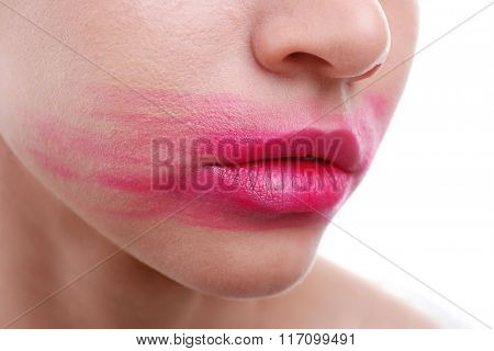 Woman's face with smeared pink lipstick isolated on white, close up