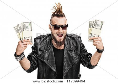 Male punk rocker holding a few stacks of money and looking at the camera isolated on white background