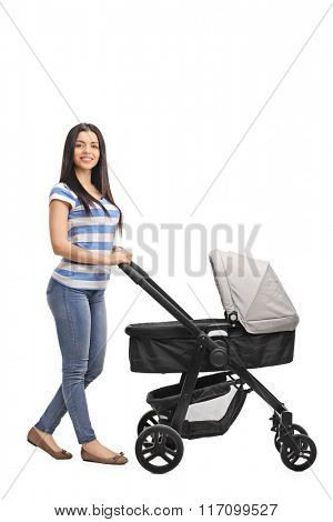 Full length portrait of a cheerful mother pushing a baby stroller and looking at the camera isolated on white background