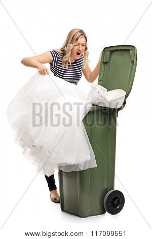 Vertical shot of an angry young woman throwing her wedding dress in the trash isolated on white background