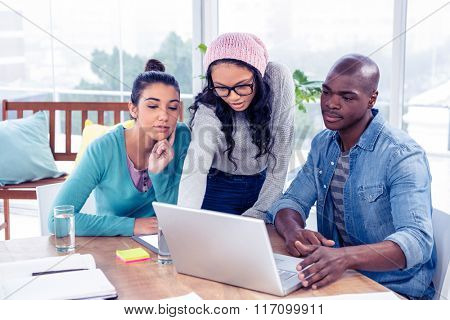 Business people looking at laptop in creative office