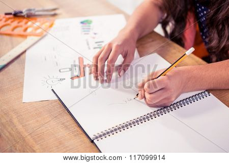 Cropped businesswoman writing in book on desk at creative office