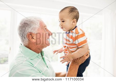 Senior man playing with his grandson at home