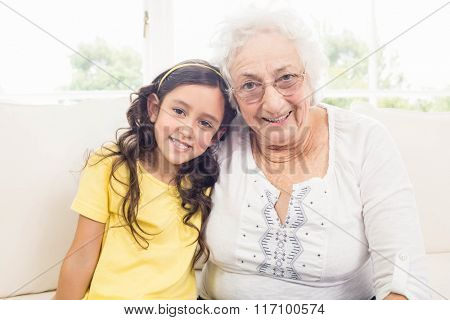 Grandmother and granddaughter smiling at home