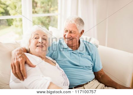 Cute senior couple hugging on sofa