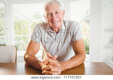 Happy senior man crossing fingers at home