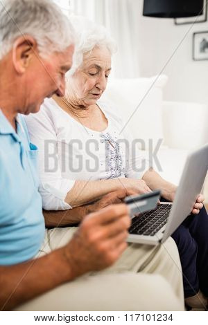 Smiling senior couple using laptop at home