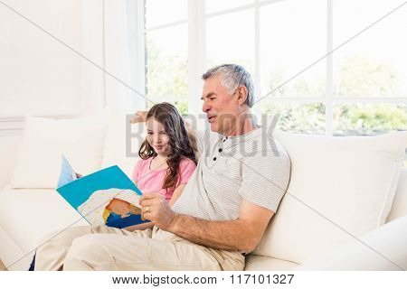 Smiling grandfather and granddaughter reading book on the sofa