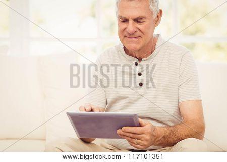 Smiling senior man using tablet on the sofa