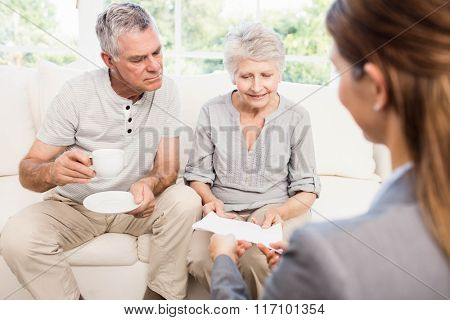 Businesswoman showing documents to senior couple at home