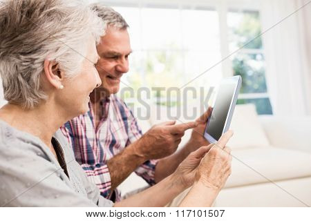 Smiling senior couple using tablet on the sofa