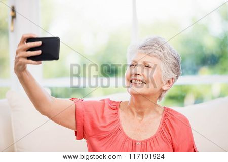 Happy senior woman taking selfie on the sofa