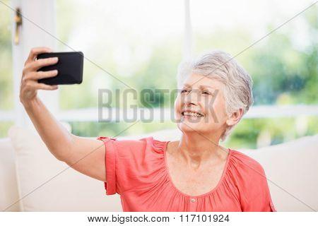 Happy senior woman taking selfie on the sofa