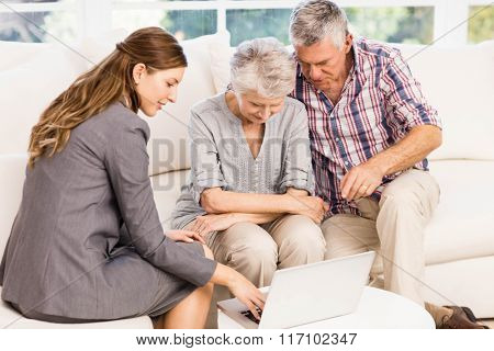 Smiling businesswoman showing laptop monitor to senior couple at home