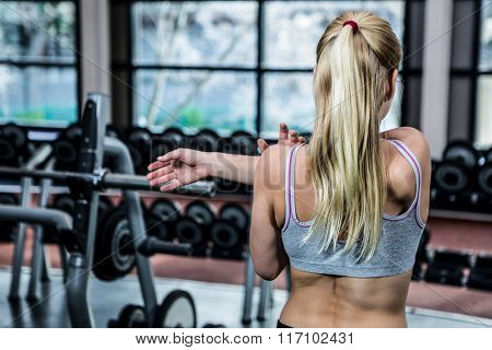 Rear view of woman stretching arms at gym