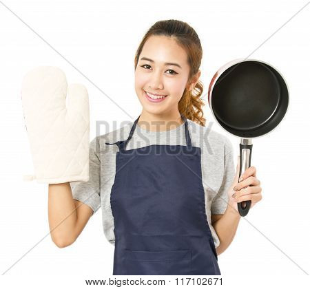 Asian Woman Wearing Apron And Showing Pot With Oven Glove.