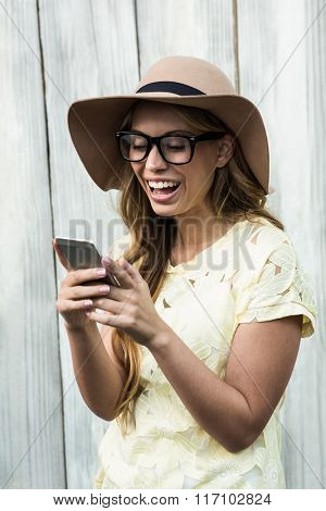 Smiling happy woman using mobile against wood background