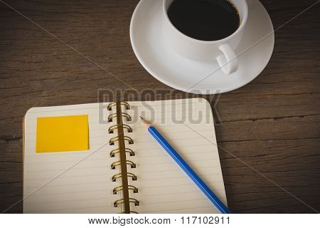 Coffee cup and note book on wooden