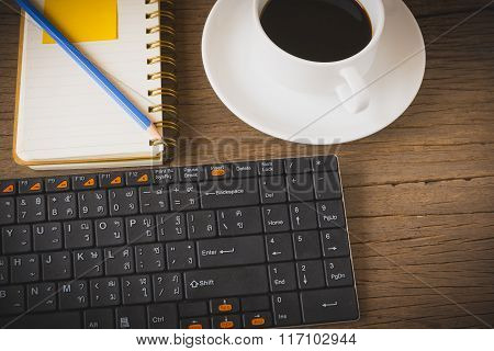Coffee cup note book and keyboard on wooden