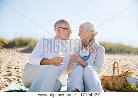 happy senior couple talking on summer beach