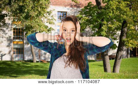 pretty teenage student girl holding to head
