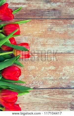 close up of red tulips on wooden background